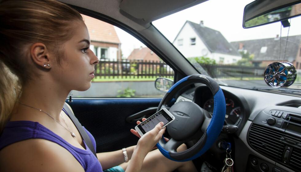 BRUKER MOBILTELEFON I BIL: Unge voksne og foreldre med hjemmeboende barn under 18 år er de verste når det kommer til ulovlig mobilbruk bak rattet. Foto: Mike Schröder / Argus / Samfoto