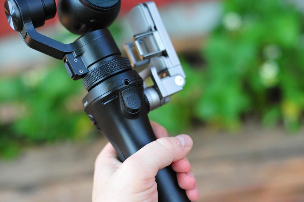 LÅS POSISJONEN: Med denne knappen, som blir liggende på pekefingeren når du holder DJI Osmo, kan du låse retningen slik at dine bevegelser ikke påvirker kameraposisjonen nevneverdig. Foto: PÅL JOAKIM OLSEN
