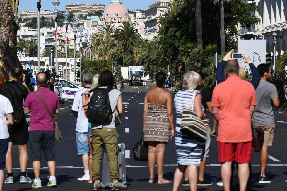 TERROR I FERIEBY: Er du i Nice, eller skal dit på ferie, kan du få hjelp av reiseforsikringen etter terrorangrepet. Her står turister dagen etter og ser på traileren som ble brukt under torsdagens angrep. Foto: ANNE-CHRISTINE POUJOULAT / AFP / NTB SCANPIX