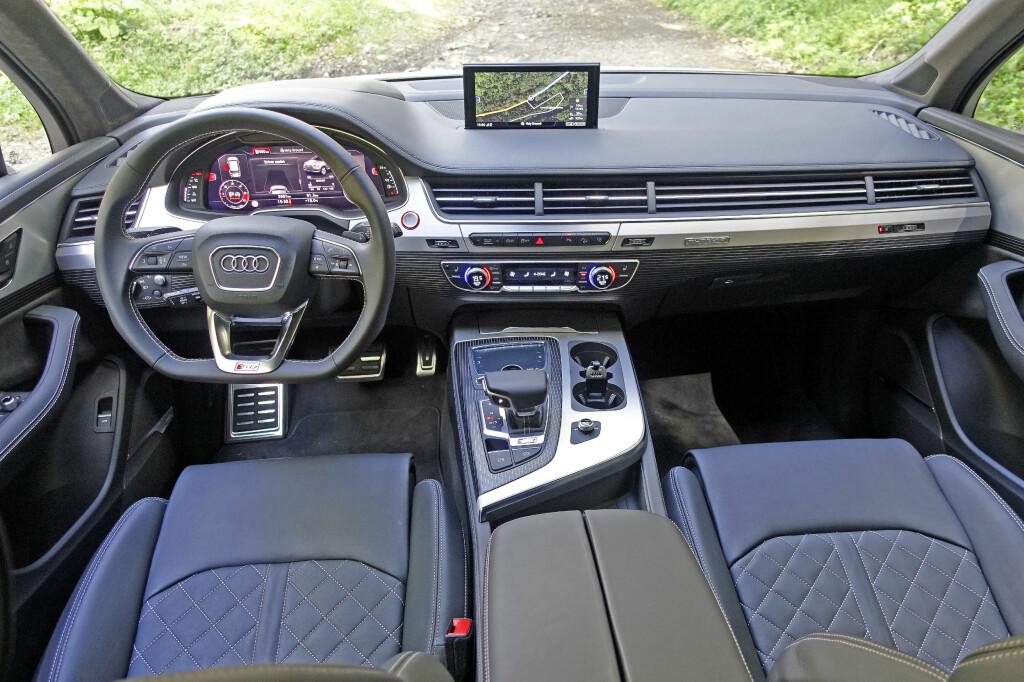 <b>CLEAN:</b> Det er ordet som faller oss inn når vi betrakter Audi-interiøret. Mye minner om lillebror A4 i denne råtassen av en Q7, bare mer massivt. Flatbunnet ratt er et must for en slik doning. Foto: KNUT MOBERG