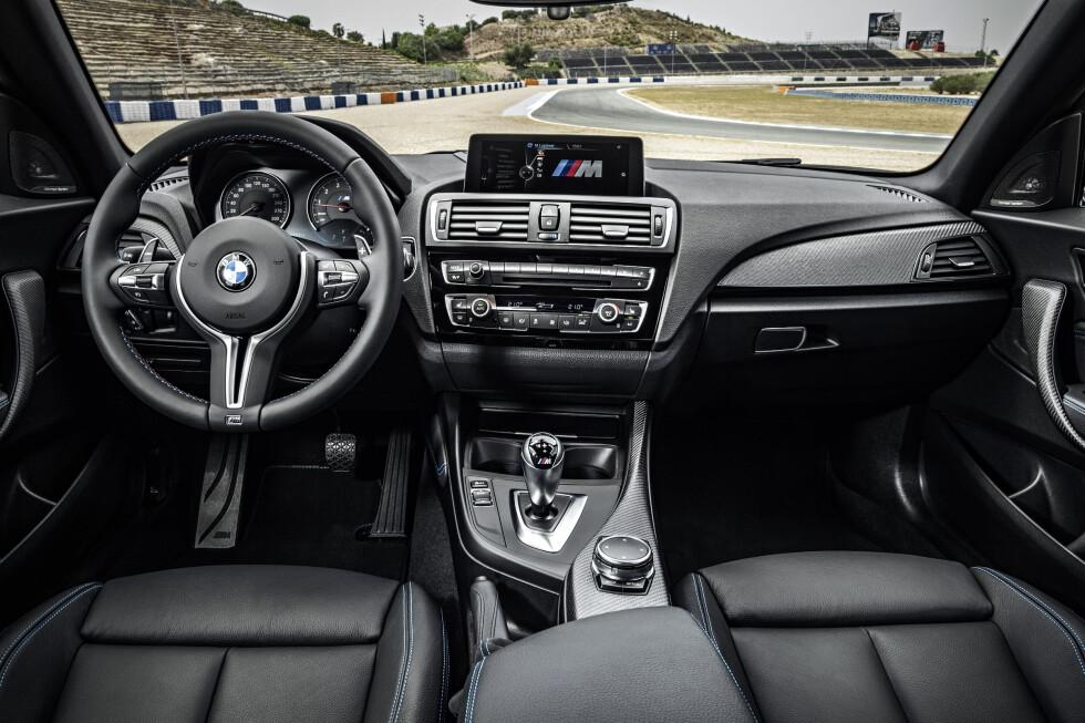 SORT: Det er ikke gjort mye for å differensere M2 fra resten av toerne, men du har egne instrumenter, røfft karboninnlegg, eget, ratt, seter og dørtrekk. Alt med blå søm. Foto: BMW