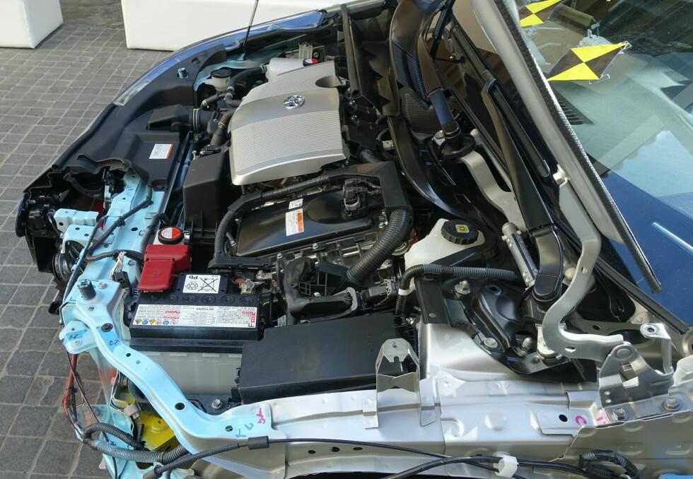 <strong><b>TETTPAKKET:</strong></b> I motorrommet ser vi bortest dekselet over bensinmotoren på 1,8 liter. På hitsiden sitter transmisjonsenheten med generator, elmotor/generator, planetgir og overføringsenhet.Elmotoren driver bilen på egenhånd ved oppstart, og i revers. Den kan drive bilen alene opptil 50 kilometer i timen. Foto: KNUT MOBERG
