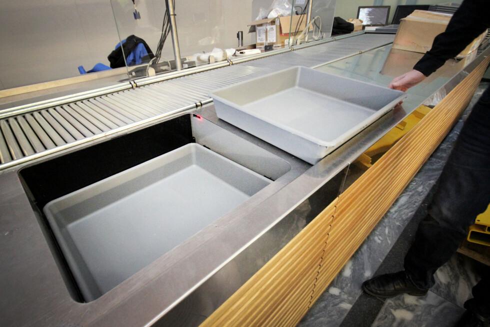 FERDIG: Når du er ferdig, skal kassene settes i disse kassemagasinene - som det finnes to av på hvert bånd. Foto: OLE PETTER BAUGERØD STOKKE