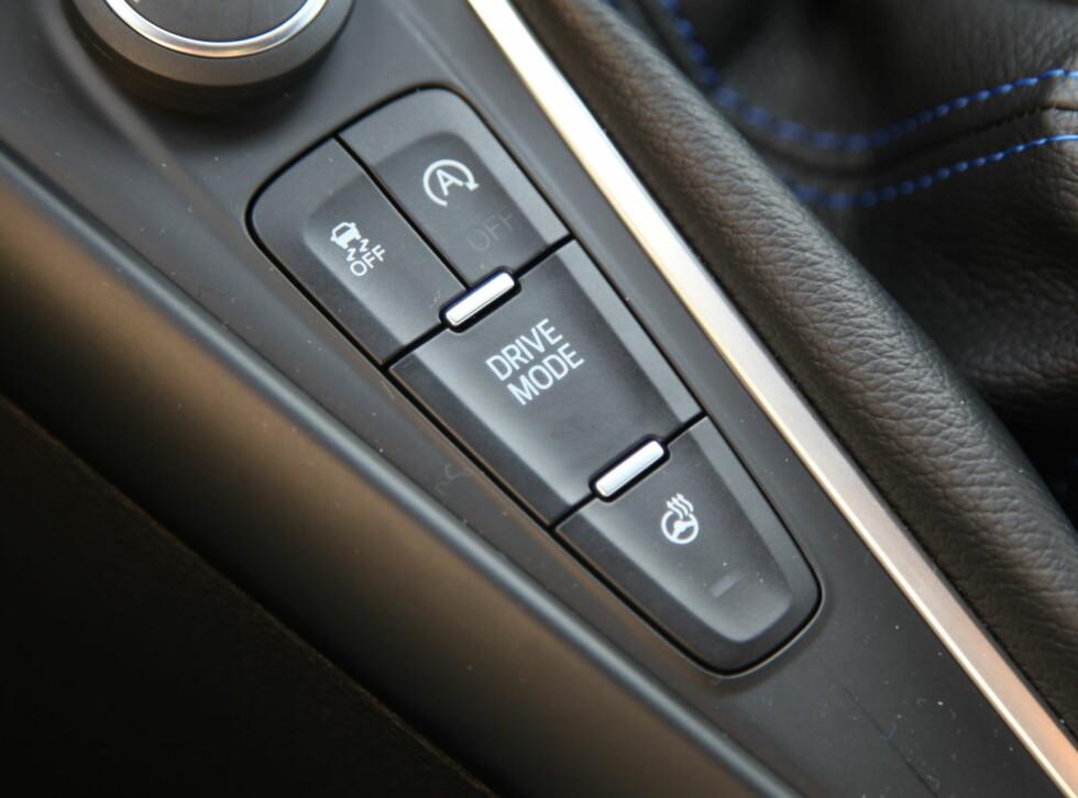 DEN MAGISKE KNAPPEN: Ved å trykke på denne kan du veksle mellom fire ulike kjøremodus. Rattvarmeknappen burde etter vår mening vært erstattet av en hurtigknapp for launch control.  Foto: KNUT ARNE MARCUSSEN