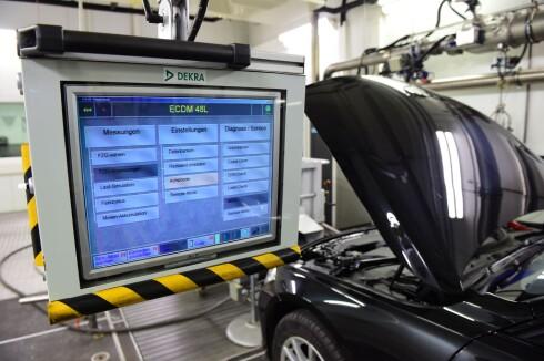 LABORATORIE-UTSLIPP: Her ser vi en bil bli preparert for utslippsmålinger etter EU-normen. Testingen gjennomføres av den uavhengige tyske sertifiseringsorganisasjonen Dekra. Foto: SCANPIX/AFP PHOTO/JOHN MACDOUGALL