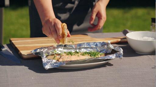 GRILLET SITRON: Nykvist skviser en halv sitron som har fått ligge med snittsiden ned på grillen over den ferdigrillete sjøørreten. Foto: ANDERS S. FOUGNER