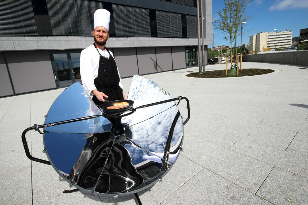 SOL OG MAT: Vår huskokk Martin Ryszard Karkus ble nysgjerrig på solgrillen og måtte ut av kjøkkenet for å teste den. Foto: OLE PETTER BAUGERØD STOKKE