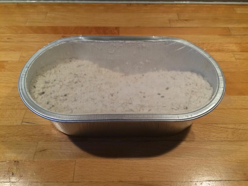 INNI PAKKEN Når vi tar av papiremballasjen sitter vi igjen med brødformen, og brødmiksen som er dekket av et tynt lag med plast. Foto: ELISABETH DALSEG