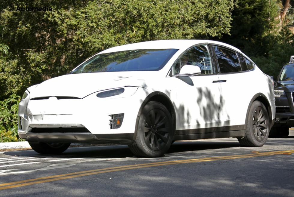 FERDIG TIL TEST: Her er Tesla Model X omsider ute på veien - bare lett forkledd. Til høsten skal den være på markedet. Og falkevingedørene vil være på plass. Foto: AUTOMEDIA