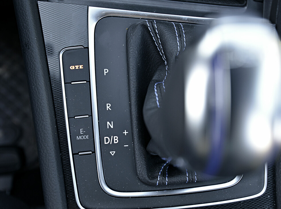 SENTRALE KNAPPER: Ved siden av 6-trinns DSG-kassen, finner du to sentrale knapper. Den ene låser bilen i el-modus. Den andre fokuserer på mest mulig ytelse og gir grom lyd. Foto: JAMIESON POTHECARY