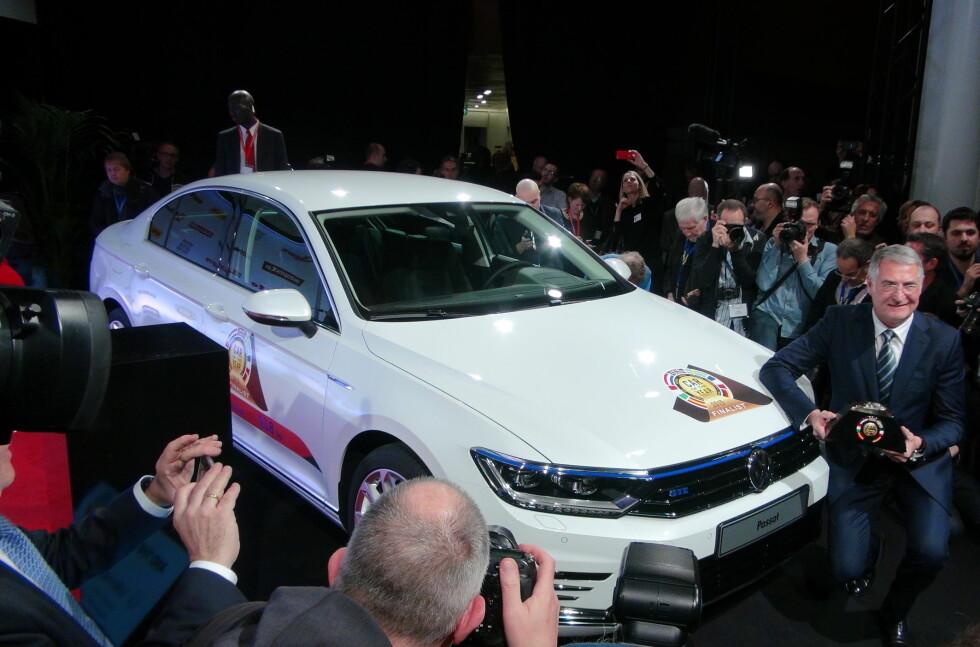 DET BLE PASSAT: Her holder utviklingssjefen i Volkswagen, Heinz-Jakob Neusser, stolt frem Car of the Year (COTY)-trofeet foran familiebilen som ble årets vinner. Foto: FRED MAGNE SKILLEBÆK