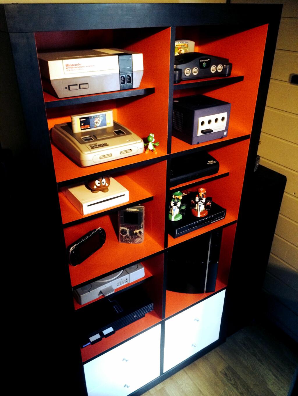 RETROHYLLE: Anders Helle har laget denne fine hyllen til sine gamle spillkonsoller. Han har satt sammen flere Ikea-hyller, og malt innsiden med vanlig interiørmaling. Foto: PRIVAT