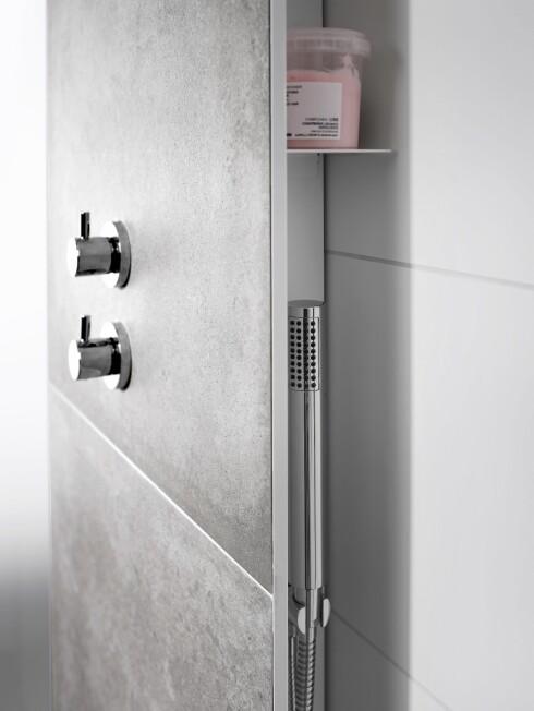 SKJULT OPPBEVARING: På hver side av veggen er det smale hyller til oppbevaring av shampo og såpe, og her henger også den håndholdte dusjen.  Foto: INR