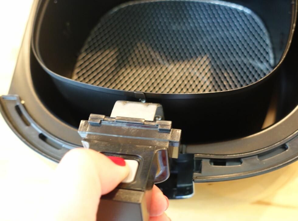 Og kurven fjernes ved å trykke på en knapp på håndtaket, og løfte den ut. Foto: ELISABETH DALSEG