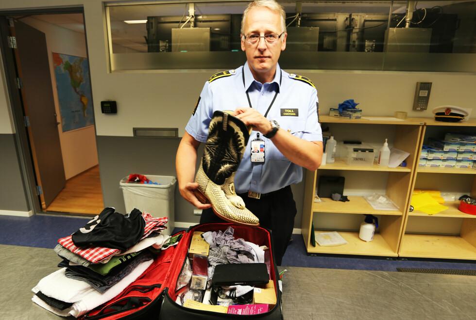IKKE KJØP ULOVLIGE SUVENIRER: Tor Fredriksen, kontorsjef for Tollvesenet på Oslo Lufthavn, viser frem beslag av ulovlige slangeskinnsprodukter. Foto: OSLO LUFTHAVN AS
