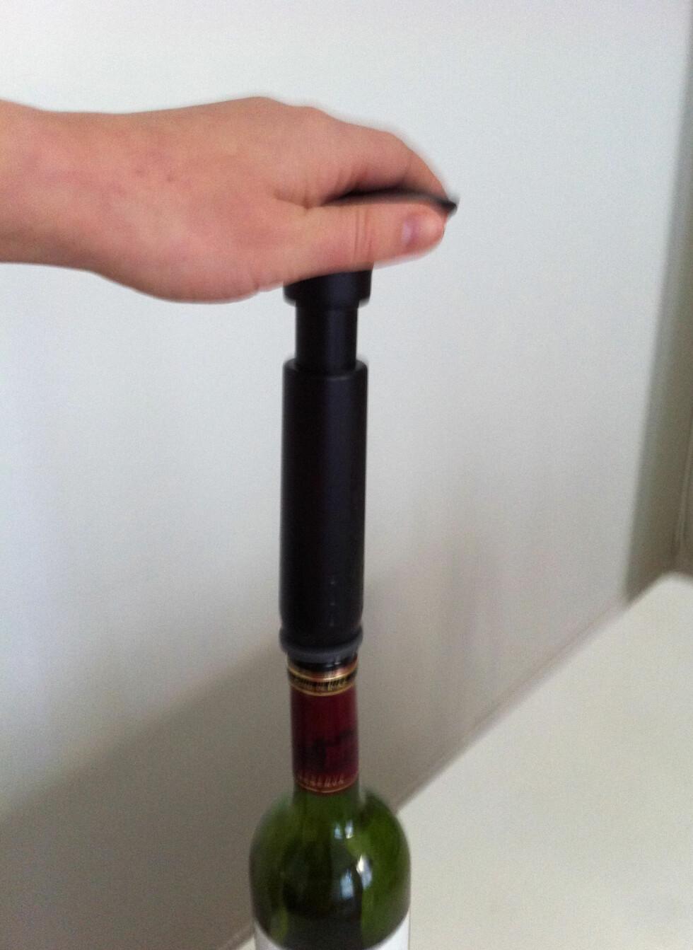 Vakuumpumpen er enkel i bruk: Trykk korken på plass, og så pumper du til det butter imot. (Du bør bruke to hender, en til å holde pumpen/flasken og en for å pumpe.) Foto: Elisabeth Dalseg