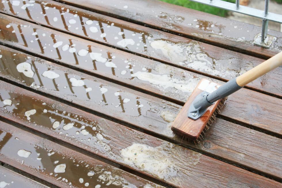 La terrasserensen ligge etter anvisning på flasken, før du skrubber med en kortbustet kost. NB Det er viktig at ikke terrasserensen tørker inn, så sprut gjerne litt vann over der du ser at treverket suger til seg all fuktigheten. Terrasserensen trenger vann for å virke.  Foto: Ifi.no