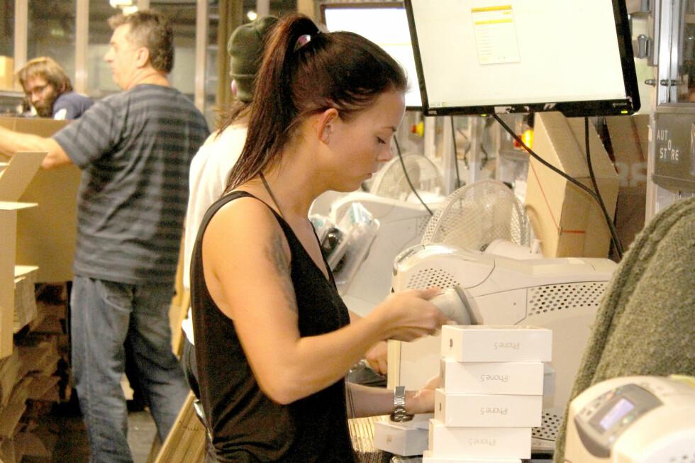 MANUELL MELLOMSTASJON: Når robotene har plukket varene sendes til arbeidere som legger dem i pappesker. Her er blant annet iPhone 5 på vei.  Foto: Ole Petter Baugerød Stokke