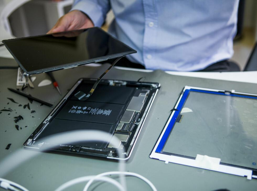 """I hånda holder Kvisli skjermen, på bordet ligger en """"naken"""" iPad med batteripakken eksponert. Ved siden av ligger det nye glasset. Foto: Per Ervland"""