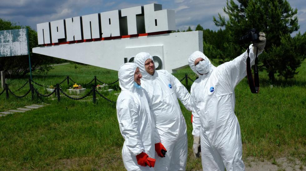 IKKE SYDEN: Her har en gruppe russisktalende turister ikledd seg fullt beskyttelsesutstyr utenfor skiltet som ønsket Tjsernobyl-arbeider velkommen til Pripjat. Neppe nødvendig, men artig på bilder. Foto: Ole Petter Baugerød Stokke