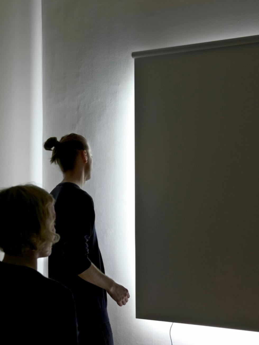 Dette er ikke et vindu som er dekket av en rullegardin, men en lampe på en hvit vegg. Screened daylight heter lampen Foto: Daniel Rybakken