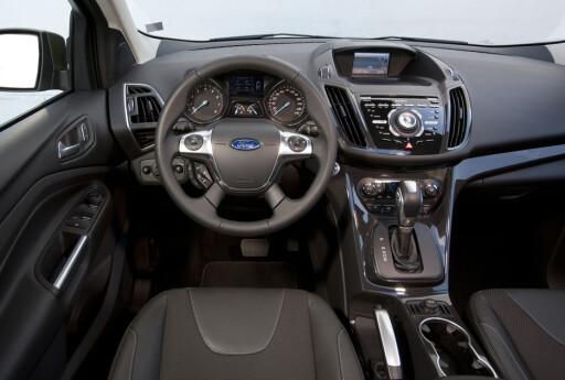 """Typisk Ford-interiør: Det er lett å finne seg til rette her og førermiljøet i nye Kuga virker mer høyverdig. Men vi er av de som er kritiske til den noe """"masete"""" layouten med en betjening som kunne vært mer enhetlig og ergonomisk. Vi synes designerne har overdrevet implementeringen av kinetisk design her."""