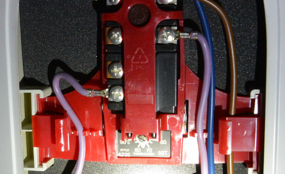 Innstillinger for termostaten befinner seg bak et sidedeksel, mellom strømførende ledninger. Foto: Brynjulf Blix