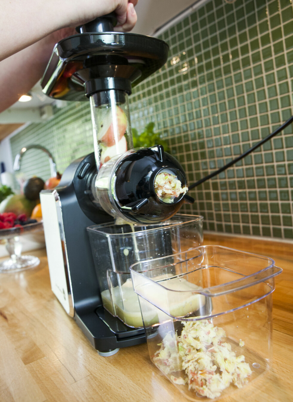 Juicen presses rett ut - og ned i en plastboks, mens avfallet kommer ut foran.  Foto: Per Ervland