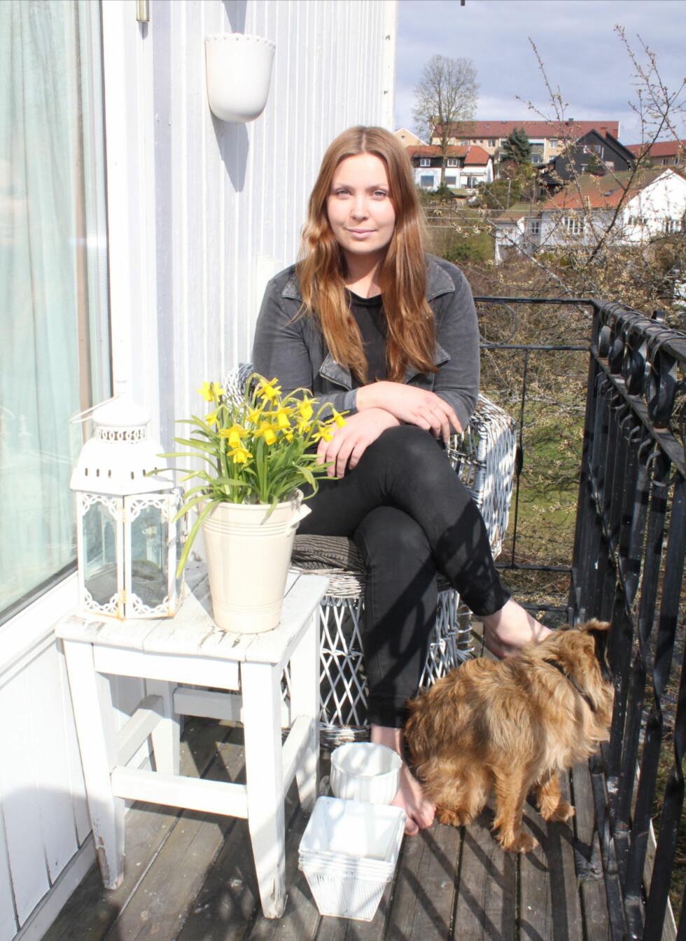 Vanja og hunden Aron. Møblene og interiøret på balkongen er fra loppemarked. Foto: Sindre K. Nordengen