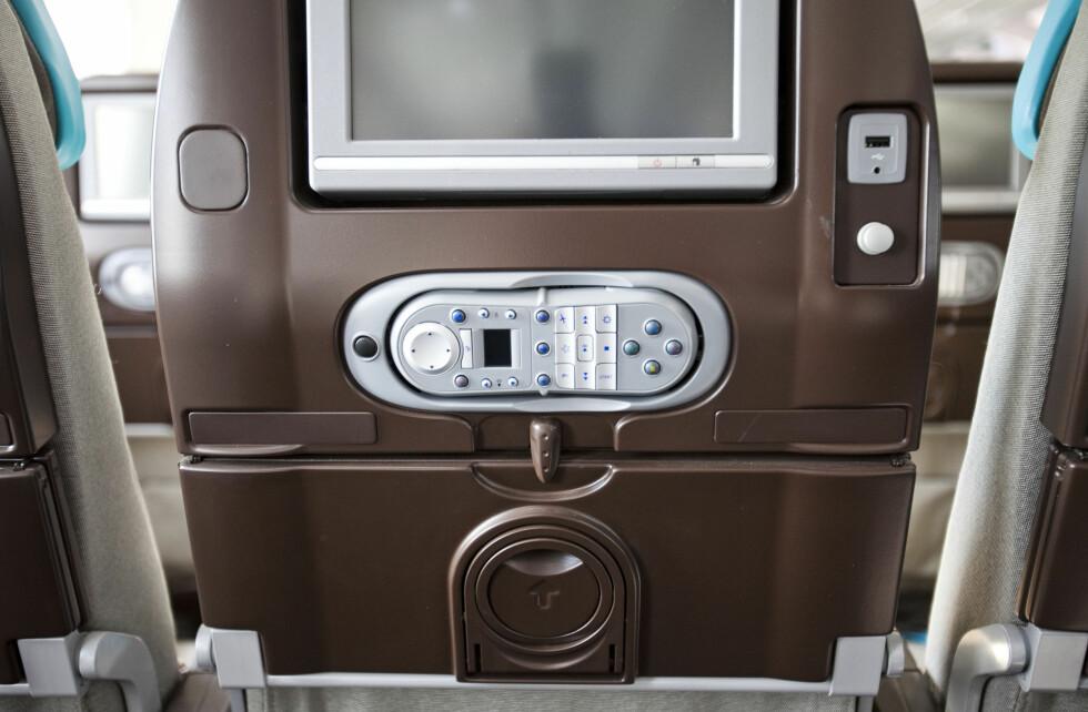 Nærbilde av TV-skjermen og fjernkontrollen på økonomiklasse. Foto: Per Ervland