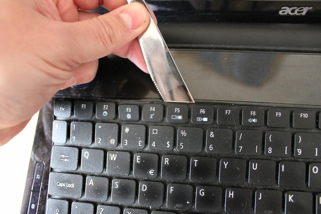 Vi brukte en smørkniv til å vippe løs tastaturplaten, men bruk gjerne noe av plast for å være helt sikker på at du ikke ødelelegger noe. Foto: Bjørn Eirik Loftås