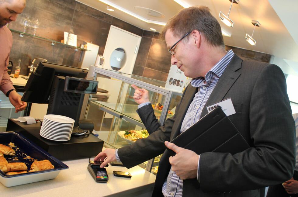 FUNGERER: Tap2Pay, som er Telenor og DNB sitt mobilbetalingssystem med NFC, fungerer allerede blant annet i Telenors kantiner. Her prøver banksjef Peer Theien i DNB seg, og får det til etter noen forsøk. – Feilen lå på andre siden av disken, forsikrer Theien og ler.  Foto: Ole Petter Baugerød Stokke
