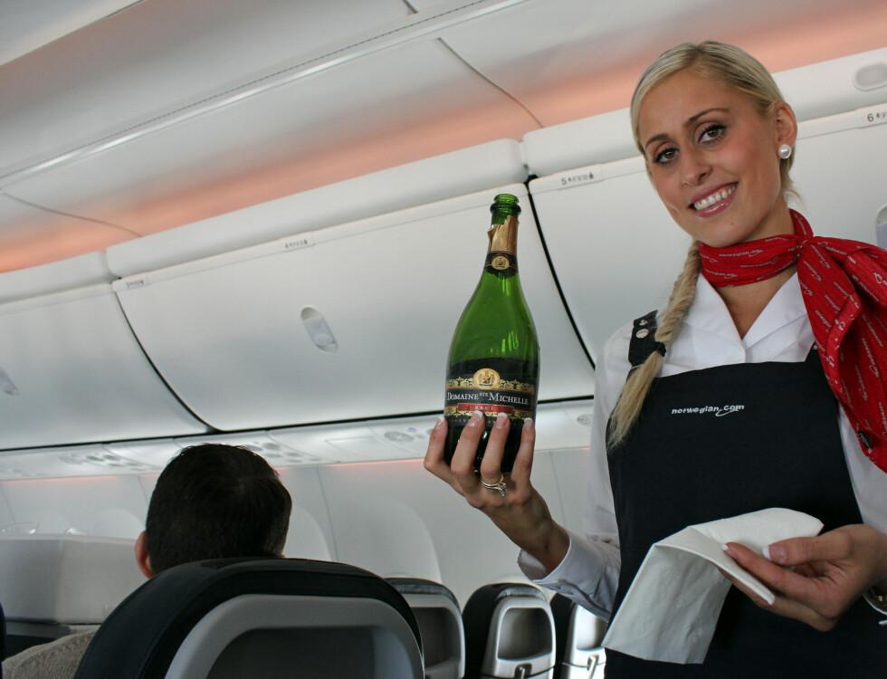 - Skal det være litt champagne? Helene Cecilie Sandberg, flyvertinne i Norwegian, byr på bobler. Foto: Silje Ulveseth
