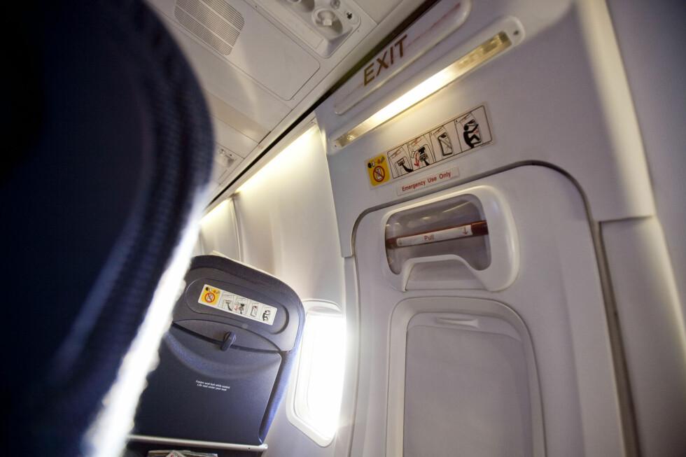 """NØDUTGANGEN: Setene ved nødutgangen er blant de mest populære setene i hele flyet. Men det er lite lurt å """"falle for fristelsen"""" og åpne opp døren ...  Foto: Per Ervland"""