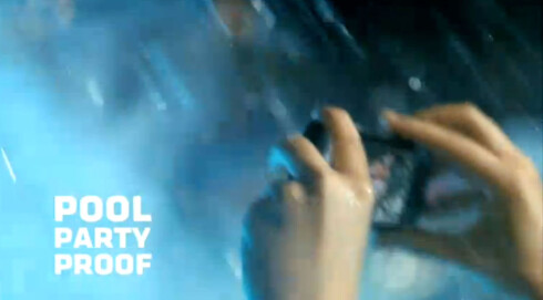 """<strong>REKLAMER:</strong> Motorola bruker aldri ordet vanntett (water proof) om Defy. Men de bruker blant annet """"pool party proof"""", og viser hvordan den kan bli splasjet full av vann. Foto: Skjermdump fra Youtube"""