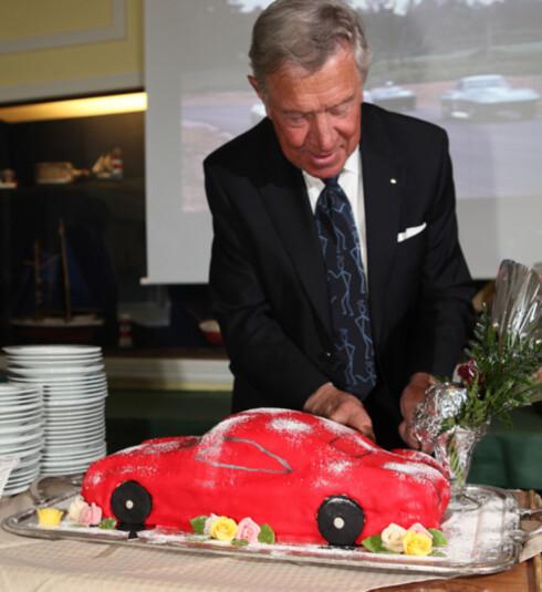 Designeren av Volvo P1800, Pelle Petterson, går løs på bursdagskaken i anledning bilens 50-årsjubileum.