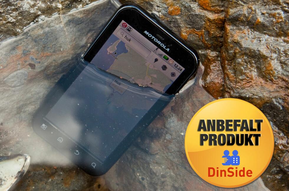 TØFFING: Motorola Defy tåler vann, sand og bank. Motorola markedsfører den ikke som vanntett, bare sprutsikker, så du bør ikke la den ligge slik alt for lenge.  Foto: Per Ervland