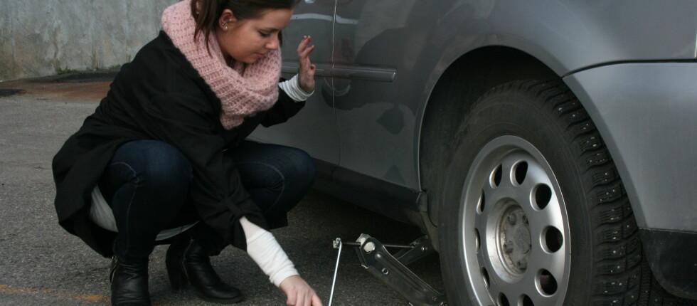 Sarah Hjorthol (24)skifter her hjul på bilen for første gang. Med noen tips og råd gikk det som smurt. Foto: Mathilde Naustvik
