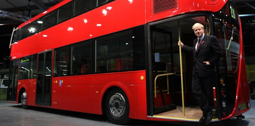 Londons borgermester Boris Johnson viser frem en modell i full størrelse. Han står ved bakdøren, som er åpen slik at folk kan hoppe av og på utenom stasjoner. Foto: London Transport Museum