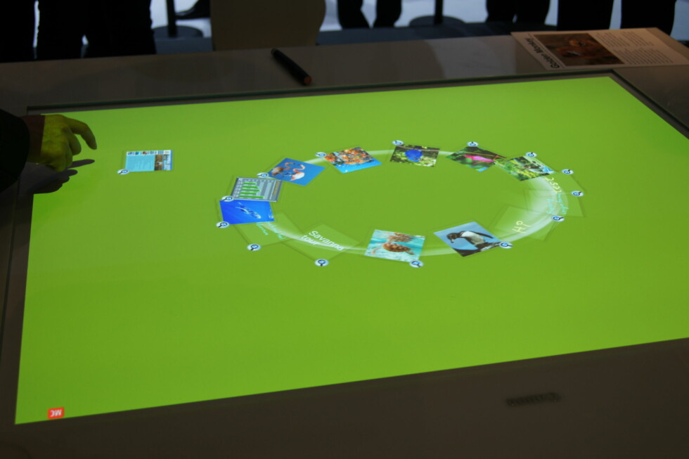 Vi fikk også se bruken av et multitouch-bord til bruk på møter etc. Her demonstreres en brainstorm-session i en bedrift, der alle kan sitte rundt bordet og dytte bilder og ideer inn i en felles ring. Foto: Pål Joakim Olsen