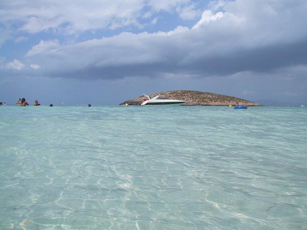 Platja de ses illetes er kjent for sitt klare vann. Her ses en av de seks øyene som har gitt stranden navn. Foto: Wikimedia Commons