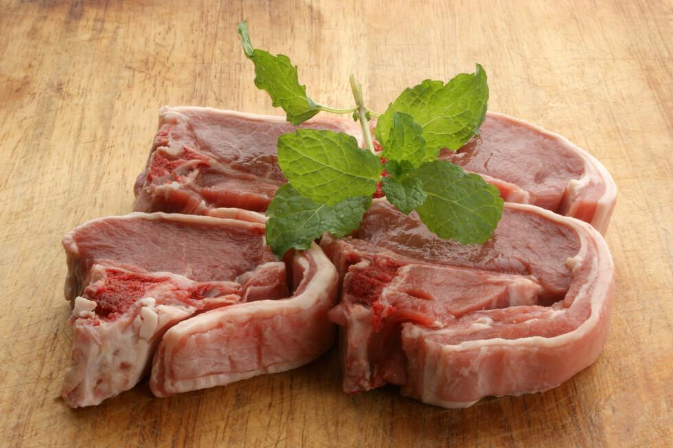 organic raw lamb chops on a timber board