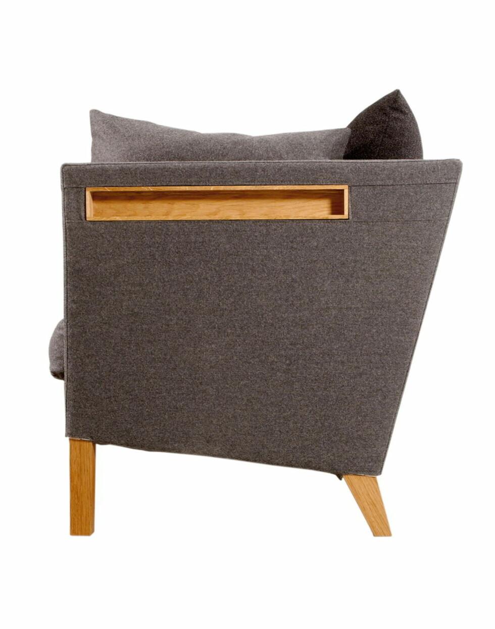 I armlenene på sofaen kledd er det innfelt små hyller. Foto: Norrgavel