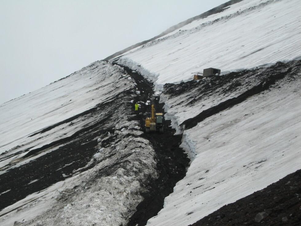 Infrastruktur:  Ved siden av stien brøytes det en kjørevei gjennom snøen for transport av brusautomater og septiktanker.