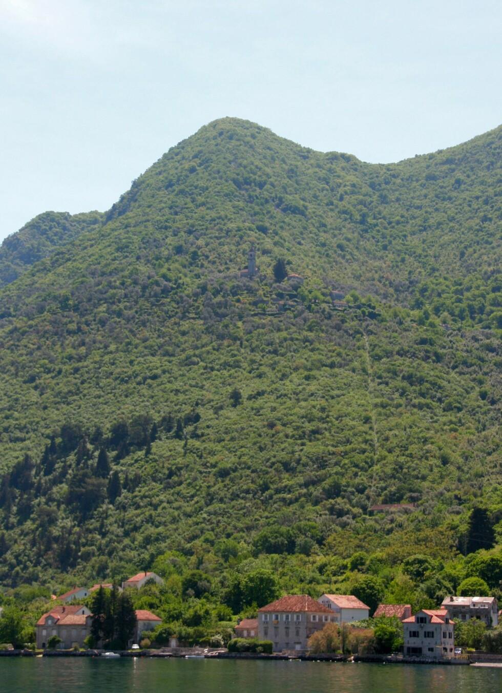 Ser du den lille landsbyen med kirke som ligger langt oppi fjellsiden? Du kan også se taubanen som går ned til landsbyen ved sjøen. Foto: Stine Okkelmo