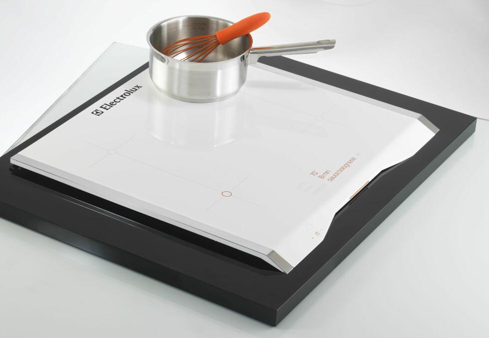 VESTA: Som mange av de andre produktene i konkurransen, skal også denne dingsen spare plass på kjøkkenet. Den sorte platen er et skjærebrett, mens den hvite toppen er en kokeplate. Kokeplaten kan løftes opp, når den ikke er i bruk. Dingsen inneholder også en scanner som leser såkalte RFID-brikker (som ifølge designeren skal erstatte strekkoder). Designeren foreslår at brikkene kan inneholde informasjon om oppskrifter og tilberedningstider. Desinet av Matthias Pinkert (Tyskland) Foto: Electrolux