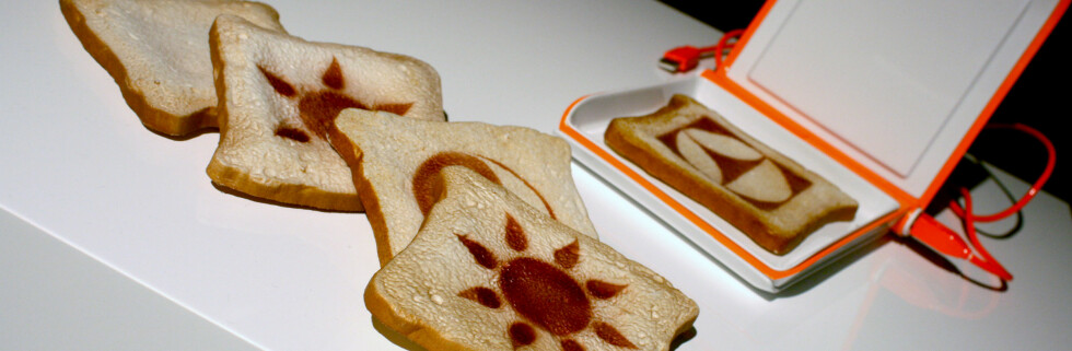 Denne brødristeren kan mer enn å varme opp brødskiva, den brenner inn motiver på maten. Hva med et bilde av mor på matpakka? Foto: Kim Jansson