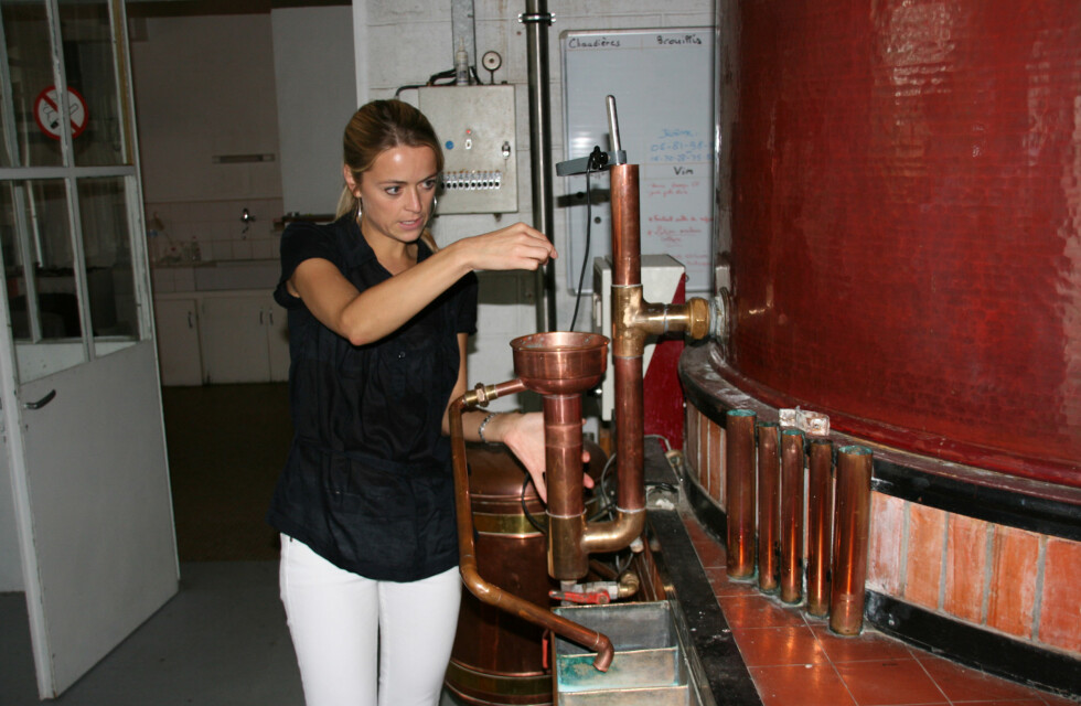 Marthe Abel viser hvordan destilleringsprosessen fungerer. Her drypper råkonjakken ut. Foto: Astrid Mannion
