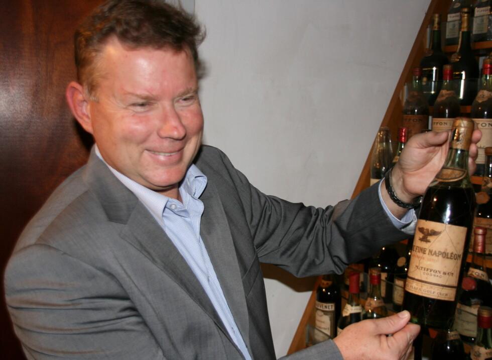Jan Braastad viser stolt frem en av de elste flaskene fra 1810. De smaker ennå fantastisk, forteller han. Foto: Astrid Mannion