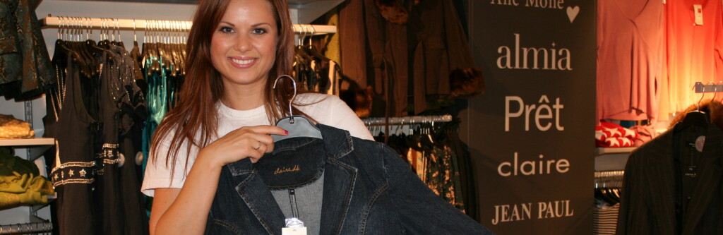 Anya Morrell, kategoriansvarlig ved dameavdelingen hos Outlet One, viser frem en jakke fra Claire. Se hvor mye du sparer på å handle her, i tabellen lenger nede i artikkelen. Foto: Kristin Sørdal
